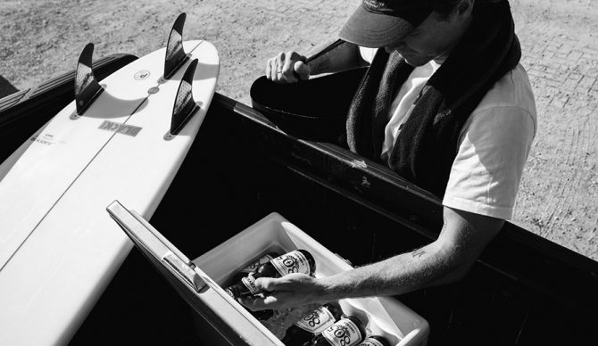 a surfer grabs a beer from the back of his truck