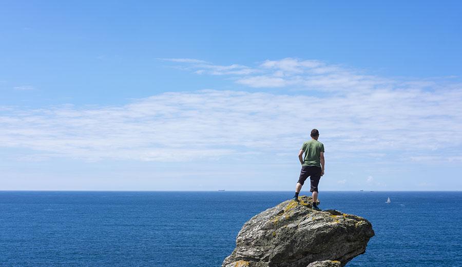 Man on rock looking at ocean