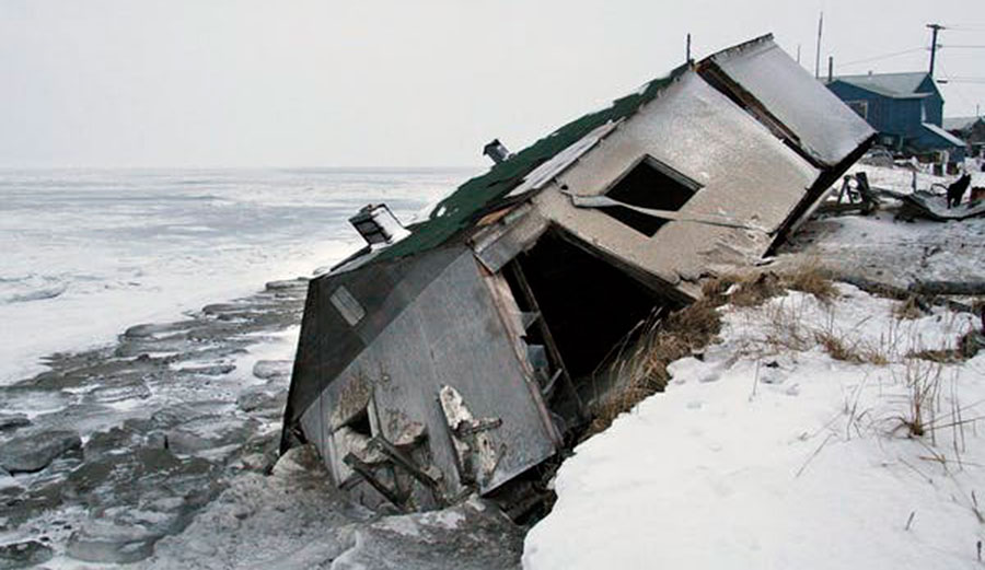 An abandoned house sits on a beach after a storm in Shishmaref, Alaska