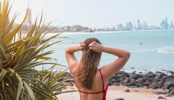 girl holding hair above surf break in australia